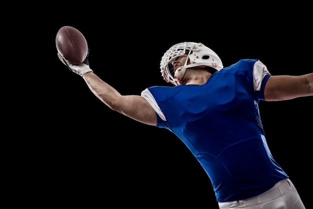 Giocatore di football con un'uniforme blu che cattura su un muro nero