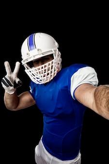 Giocatore di football americano con un'uniforme blu che fa un selfie su una parete nera