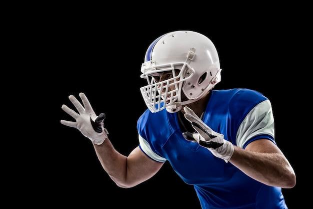 Giocatore di football americano con un'uniforme blu che fa un placcaggio su una parete nera