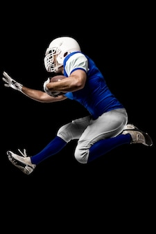 Giocatore di football americano con una divisa blu in esecuzione su un muro nero