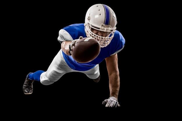 Giocatore di football americano con un'uniforme blu che segna su un muro nero