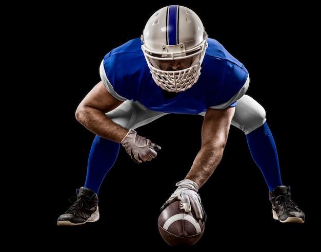 Giocatore di football con una divisa blu sulla scrimmage line su un muro nero