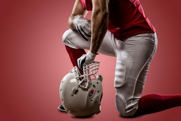Giocatore di football americano con una divisa rossa sulle ginocchia su un muro rosso