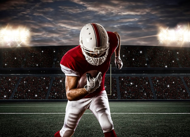 Giocatore di football americano con un'uniforme rossa in esecuzione su uno stadio.