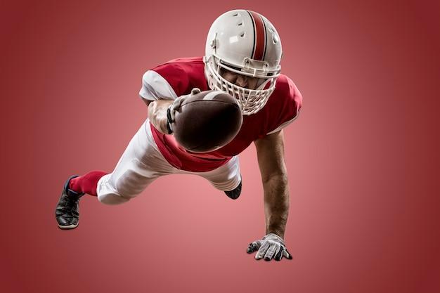Giocatore di football americano con un'uniforme rossa che segna su una parete rossa