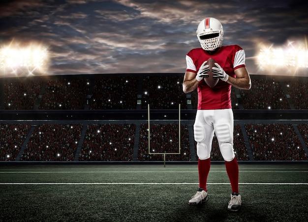 Giocatore di football americano con un'uniforme rossa su uno stadio.
