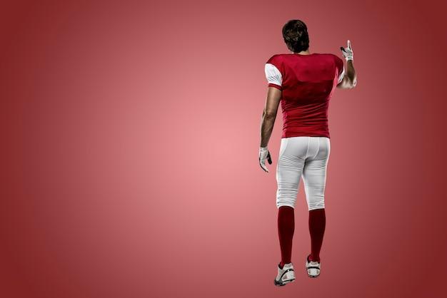 Giocatore di football americano con un'uniforme rossa che cammina, mostrando la schiena su un muro rosso