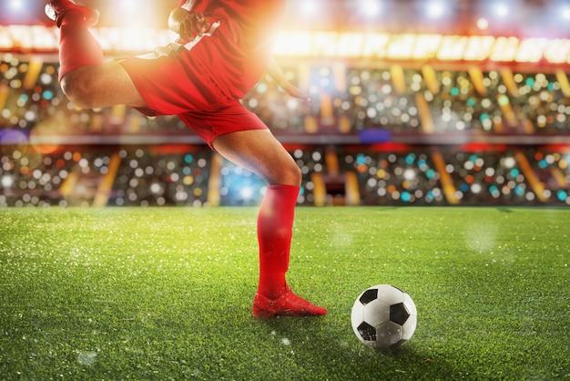 Scena di calcio durante la partita notturna con il giocatore che calcia il pallone con potenza.