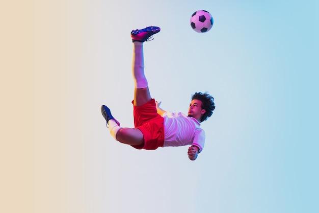 Giocatore di calcio o di calcio sfumato alla luce al neon