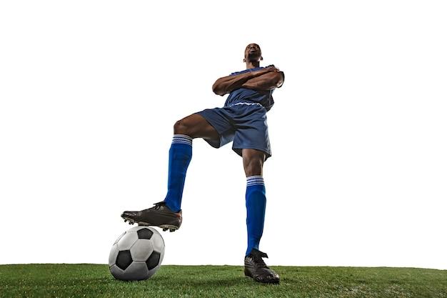 Giocatore di gioco del calcio o di calcio sul muro bianco con erba. angolo ampio.