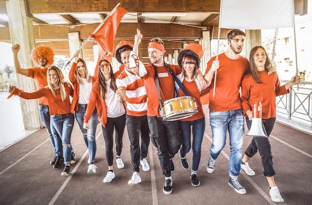 Amici di tifosi sostenitori di calcio che tifano e camminano alla partita di coppa di calcio allo stadio internazionale