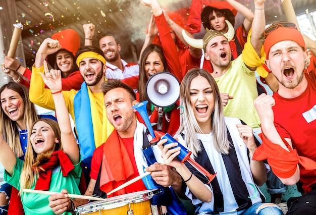 Amici di tifosi sostenitori di calcio tifo e guardando la partita di coppa di calcio allo stadio internazionale