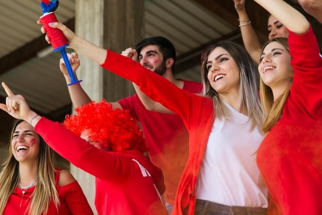 Sostenitori di calcio allo stadio - gli appassionati di calcio si divertono e guardano la partita di calcio