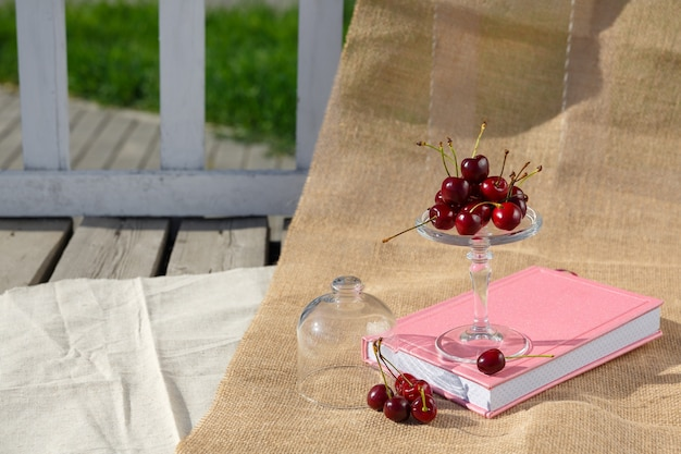 Il piatto di servizio con piedi e la mini cupola con bacche di ciliegia sono su libro e su tela su pavimento di legno