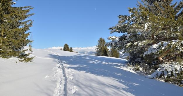 Impronta nella neve fresca che attraversa la montagna dalle vette innevate sotto il cielo blu