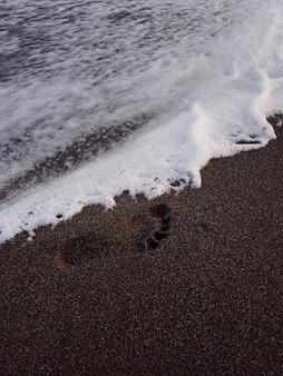 Orme sulla spiaggia durante il tramonto in estate
