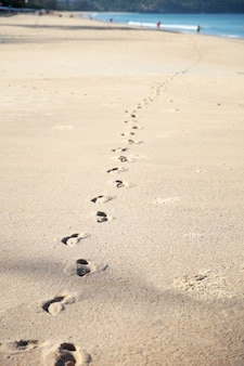Orme sulla sabbia chiara della spiaggia del mare in una giornata di sole