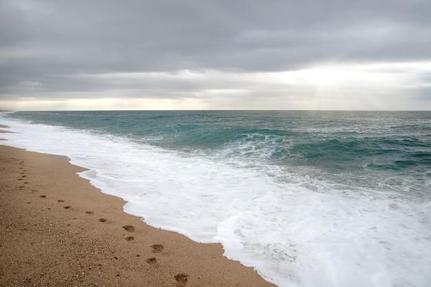 Orme sulla sabbia sulla spiaggia deserta. sfondo naturale