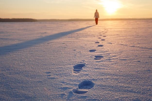 Orme nella neve. la ragazza parte verso il tramonto.