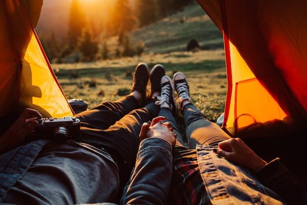 Foots di giovani coppie che si trovano in tenda per escursioni in montagna durante il tramonto.
