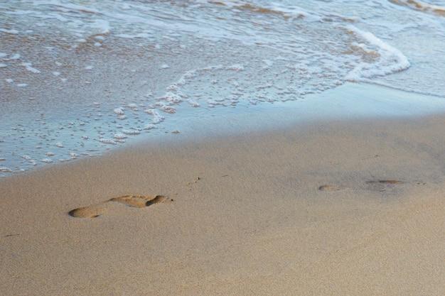 Orme sulla spiaggia in riva al mare in estate. impronte nude sulla spiaggia