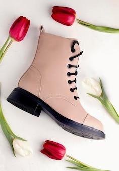 Calzature. stivali primaverili su uno sfondo bianco con fiori di tulipano