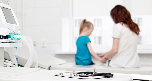 In primo piano c'è uno stetoscopio sullo sfondo il dottore tiene le mani delle ragazze