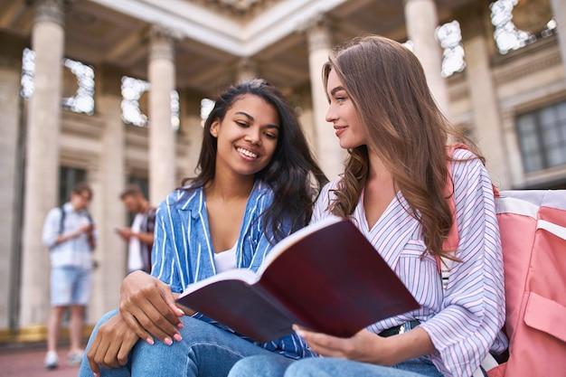 In primo piano, due conoscenti condividono le loro impressioni su un'opera letteraria