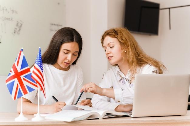 Studio privato di una scuola straniera con una ragazza della scuola. l'insegnante spiega la grammatica della lingua madre utilizzando il laptop
