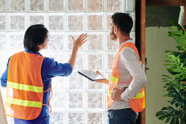 Foreman accepring lavoro di builder finitura posa del muro di mattoni di vetro in appartamento