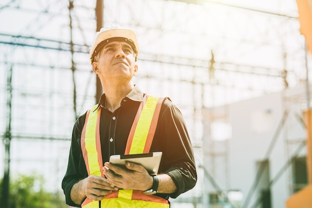 Caporeparto ingegnere costruttore lavoratore guardando grande cantiere giornata di sole duro lavoro.