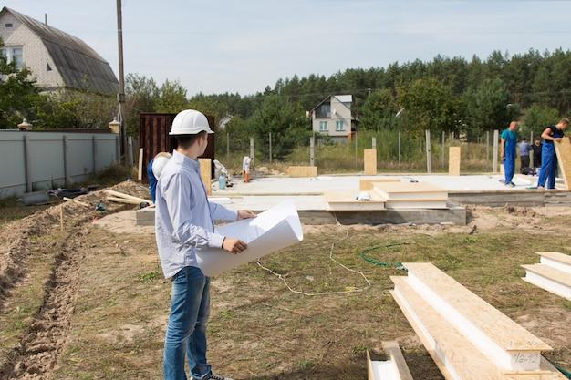 Caposquadra che controlla i materiali da costruzione sul posto in piedi di fronte a una pila di legname e legname con un progetto nelle sue mani a guardare gli operai che lavorano
