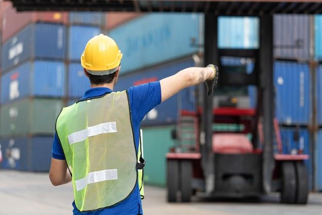 Il caposquadra usa il segnale manuale per caricare i contenitori del carrello elevatore in una scatola di container di carico