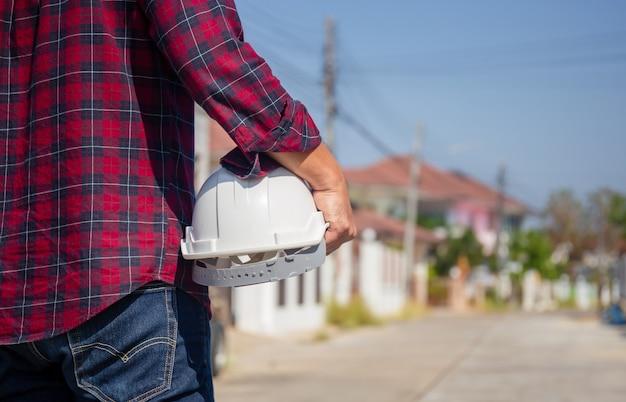 Operaio caposquadra tenere con il casco in cantiere, architetto uomo che tiene il casco di sicurezza in mano