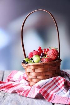 Frutti di bosco nel cesto di vimini, sul tavolo di legno, su sfondo luminoso