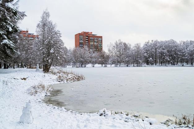 Foresta ricoperta di neve. grattacieli in mattoni rossi sulla riva di un lago ghiacciato d'inverno. paesaggio invernale in lettonia. jugla, riga