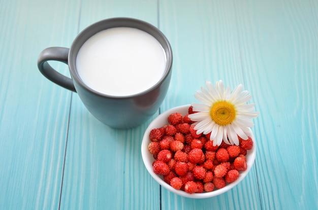 Fragole di bosco, fiori di camomilla, latte in tazza su fondo di legno, vista dall'alto. colazione salutare