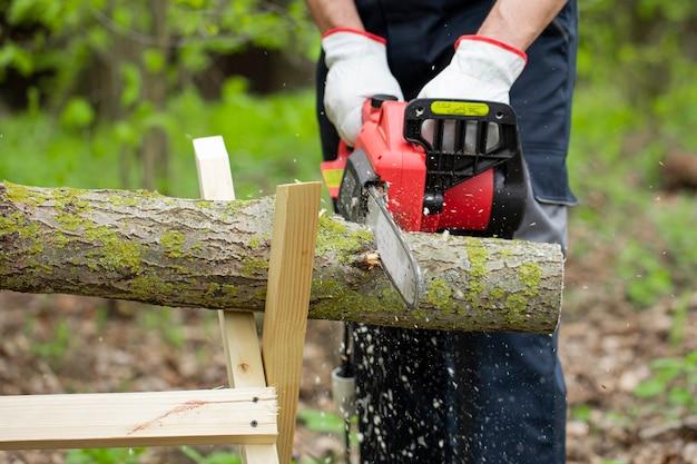 Lavoratore forestale in abbigliamento da lavoro di sicurezza protettiva sega il tronco di albero con la motosega
