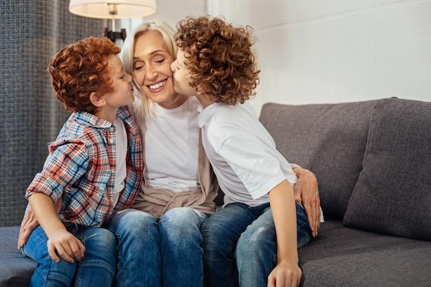 Per sempre grato. ragazzi dai capelli ricci che baciano le guance della nonna mentre sono tutti seduti su un divano e le esprimono il loro amore a casa.