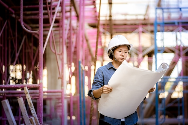 La caporeparto ispeziona il cantiere. modello della tenuta della donna di ingegneria che sembra disposizione del disegno. donna che indossa il casco di sicurezza.