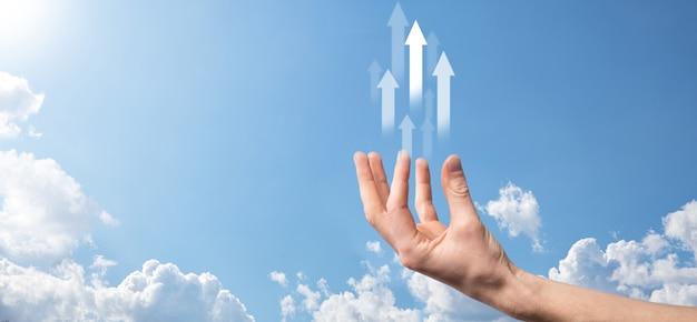 Il concetto di mercato forex con la mano dell'uomo d'affari trasporta lo schermo del tablet digitale e grafici e frecce del grafico finanziario virtuale. mano che tiene una freccia in aumento, che rappresenta la crescita del business.
