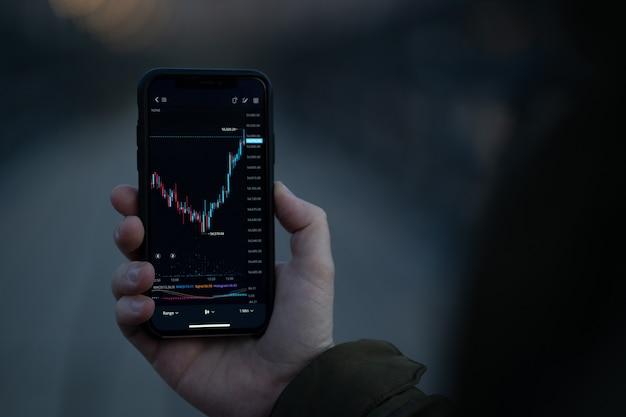 Commercio di forex. mano maschile che tiene smartphone con grafico a candele sullo schermo, trader che legge notizie finanziarie e controlla i dati del mercato dei cambi in tempo reale nell'app mobile mentre si trova all'aperto