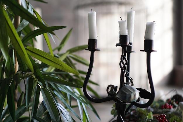 Candeliere in metallo forgiato con candele su sfondo sfocato con luce dalla finestra