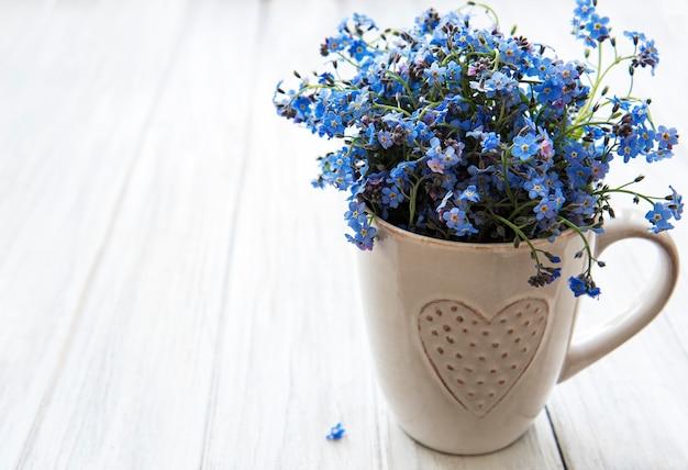 Non ti scordar di me fiori in una tazza sul tavolo