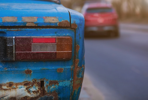 Automobile arrugginita dimenticata sulla strada. vecchia automobile arrugginita abbandonata sulla strada luci posteriori