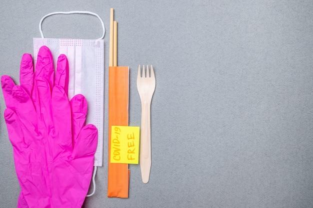 Forchetta, bacchette, una mascherina medica e guanti di lattice rosa