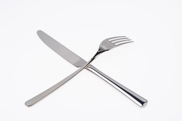 Forchetta e coltello isolati su bianco.