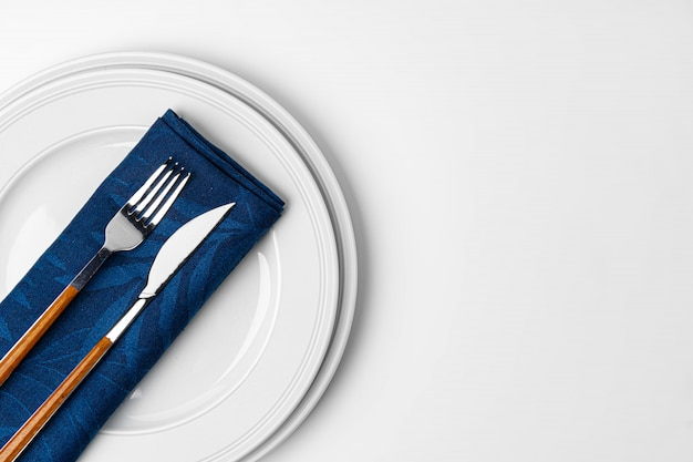 Forchetta, coltello e piatto sull'asciugamano. isolato su sfondo bianco