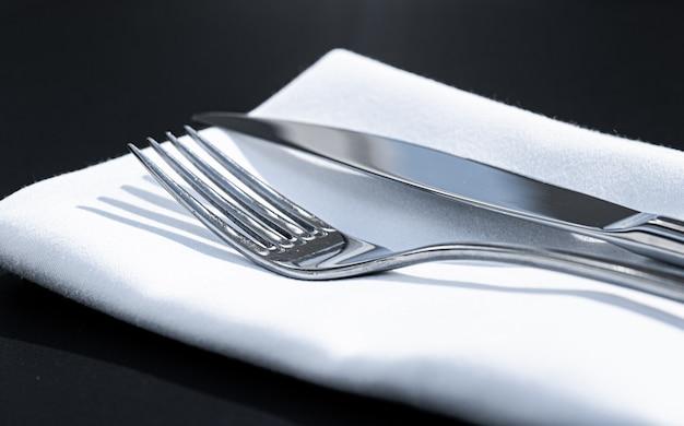 Forchetta e coltello con tovagliolo bianco sul tavolo in un ristorante di lusso all'aperto menu raffinato per matrimoni...