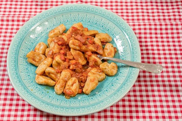 Forchetta su un piatto di gnocchi fatti in casa con salsa di pomodoro. cibo italiano.